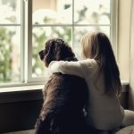 Young girl with dog at window